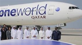 Qatar Airways Chief Executive Akbar Al Baker (3rd R), Qatar's Prime Minister Sheikh Abdullah bin Nasser bin Khalifa al-Thani (4th R), Qatar's Minister of Energy and Industry Mohammed Saleh al-Sada (2ndR) and other delegates pose in front of a Qatar Airways Boeing 777-300 aircraft during a ceremony to mark the alliance of Qatar Airways with the oneworld grouping at the Hamad International airport in Doha October 29, 2013. REUTERS/Fadi Al-Assaad