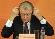 Hein Verbruggen, Chairman of the International Olympic Committee (IOC) Coordination Commission, puts on his headphones during a news conference in Beijing October 25, 2007. REUTERS/David Gray