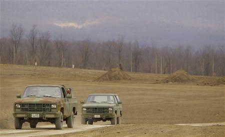 Munitions destroyers drive away from munitions ordinance (rear) under dirt mounds that will be destroyed at the U.S. Army Letterkenny Munitions Center in Chambersburg, Pennsylvania November 19, 2012. REUTERS-Gary Cameron