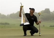 Henrik Stenson of Sweden poses with his trophies after winning the DP World Tour Championship in Dubai November 17, 2013. REUTERS/Caren Firouz
