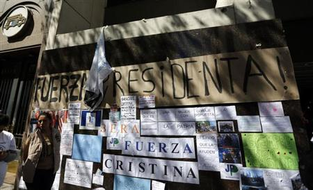 A woman waits next to signs in support of Argentina's President Cristina Fernandez outside the hospital where she had surgery in Buenos Aires October 8, 2013. REUTERS/Marcos Brindicci