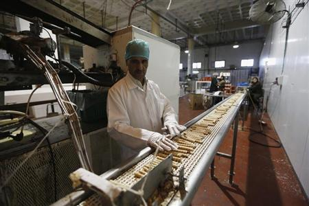 A worker stands near a conveyor belt at a chocolate and baked goods factory in the West Bank city of Ramallah October 27, 2013. REUTERS/Mohamad Torokman