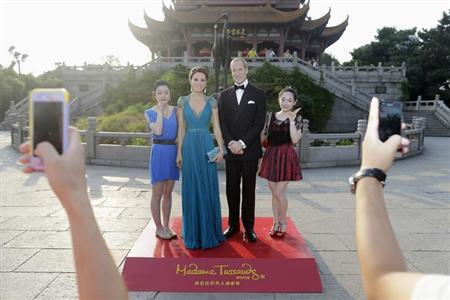 Visitors pose for photographs next to Madame Tussauds' wax figures of Britain's Prince William (2nd R) and his wife Catherine (2nd L), Duchess of Cambridge, in front of the Yellow Crane Tower during a promotional event in Wuhan, Hubei province August 13, 2013. REUTERS/Stringer/Files