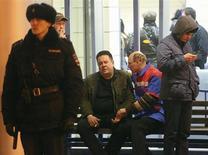 Медик справляется о самочувствии мужчины на скамейке в аэропорту Казани, где разбился пассажирский Boeing 737 17 ноября 2013 года. Следователи в понедельник продолжили просеивать обуглившиеся обломки лайнера Boeing 737-500 в поиске объяснений катастрофы, унесшей 50 жизней и укрепившей позиции России в мировом антирейтинге авиапроисшествий. REUTERS/Yegor Aleev