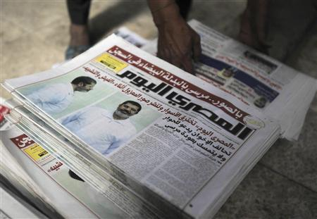 A shopkeeper sells copies of the daily newspaper Al-Masry Al-Youm with pictures of ousted Egyptian President Mohamed Mursi in white prison uniform on the front page, along Mohamed Mahmoud street near Tahrir Square in Cairo, November 18, 2013. REUTERS/Amr Abdallah Dalsh