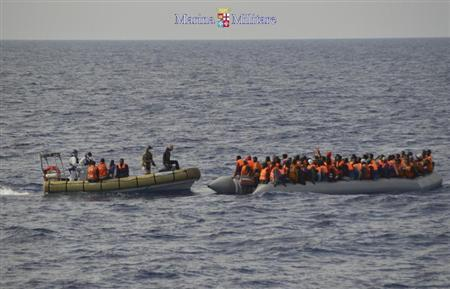 Migrants sit in boats during a rescue operation by Italian navy ship Cigala Fulgosi off the coast of the south of the Italian island of Sicily in this October 30, 2013 picture provided by the Italian Marina Militare. REUTERS/Marina Militare/Handout via Reuters