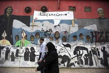 People walk in front of a mural depicting victims of the Egyptian uprising at Mohamed Mahmoud street near Tahrir Square in Cairo, November 18, 2013. REUTERS/Amr Abdallah Dalsh