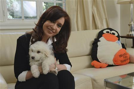 Argentine President Cristina Fernandez poses with her dog at the Olivos Presidential residence in Buenos Aires in this November 18, 2013 handout supplied by the Argentine Presidency. REUTERS/Argentine Presidency/Handout via Reuters