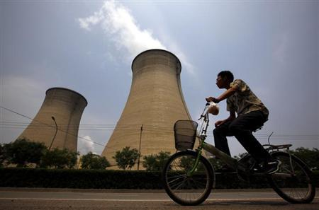 A man rides his bicycle past the cooling tower and chimneys from a coal-burning power station in Beijing June 1, 2012. REUTERS/David Gray/Files
