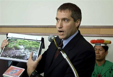 Attorney Steven Donziger shows pictures of a pool of oil which has seeped out from an oil waste pit left behind by Texaco at an oil pump site near the Amazonian jungle in Quito, Ecuador, October 30, 2003. REUTERS/Franklin Jacome