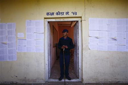 A police personnel recruited for the Constituent Assembly election, stands guard at a polling station a day before the election in Bhaktapur November 18, 2013. REUTERS/Navesh Chitrakar