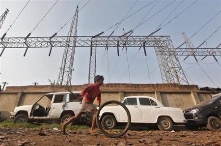 A boy plays with a tyre in front of electric pylons installed at a power house in Kolkata February 21, 2013. REUTERS/Rupak De Chowdhuri/Files