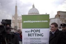 A man holds an advertisement for Paddy Power, an Irish bookmaker, in front of St Peter's square, outside the Vatican February 12, 2013. REUTERS/Max Rossi