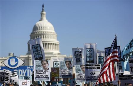Demonstrators hold up their signs during the ''Stop Watching Us: A Rally Against Mass Surveillance'' march near the U.S. Capitol in Washington, October 26, 2013. REUTERS/Jonathan Ernst