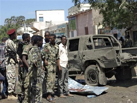 Somali policemen stand next to a damaged car at the scene of an explosion in Baladweyne in central Somalia November 19, 2013. REUTERS/Stringer