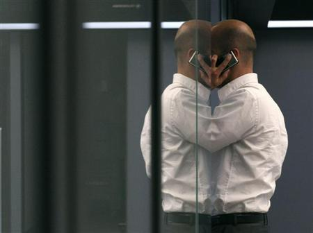 A bourse trader uses a cell phone during a trading session on the trading floor at Frankfurt's stock exchange August 2, 2011. REUTERS/Ralph Orlowski