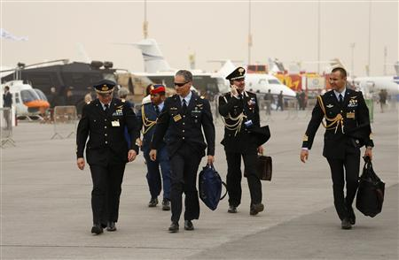 Military visitors walk during the sandstorm at the Dubai Airshow November 17, 2013. The flying display was cancelled due to the sandstorm. REUTERS/Ahmed Jadallah