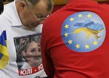 Оппозиционные депутаты в в футболках с изображением экс-премьера Украины Юлии Тимошенко и символикой ЕС на сессии парламента в Раде 8 ноября 2013 года. ЕС обещает Украине поставки газа из Словакии. REUTERS/Gleb Garanich