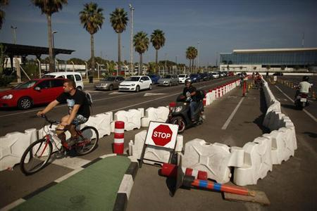 Cars wait in line to enter to Spain at its border with the British territory of Gibraltar, before the arrival of European Commission officials (not pictured) to check the border of Spain (L), in Gibraltar September 25, 2013. REUTERS/Jon Nazca