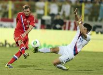 Park Jong-woo (R) of South Korea fights for the ball with Dmitry Tarasov of Russia during their international friendly soccer match at Al Wasl Stadium in Dubai November 19, 2013. REUTERS/Mohammed Omar