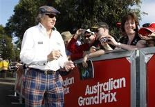 Former Formula One champion driver Jackie Stewart of Britain signs autographs as he arrives at the Albert Park circuit for the third practice and qualifying sessions of the Australian F1 Grand Prix in Melbourne March 17, 2012. REUTERS/Brandon Malone