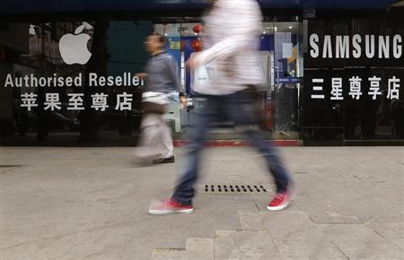 People walk past a mobile phone store selling Apple and Samsung products in Wuhan, Hubei province April 18, 2013. REUTERS/Stringer