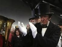 A re-enactor portraying former U.S. President Abraham Lincoln applauds a military band while being welcomed at the Gettysburg, Pennsylvania train station November 18, 2013. REUTERS/Gary Cameron