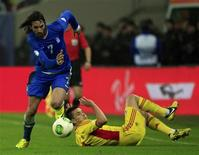 Georgios Samaras (L) of Greece controls the ball past Ovidiu Hoban of Romania during their 2014 World Cup qualifying soccer match in Bucharest November 19, 2013. REUTERS/Radu Sigheti