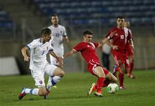 Gibraltar's Jeremy Lopez (R) fights for the ball with Slovakia's Pavol Farkas during their international friendly soccer match at Algarve stadium near Faro November 19, 2013. REUTERS/Rafael Marchante