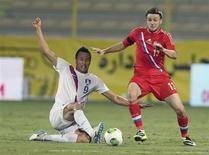 Игрок сборной Южной Кореи Ким Шин-Вук (слева) борется за мяч с россиянином Владимиром Гранатом в товарищеском матче в Дубае 19 ноября 2013 года. Сборная России по футболу одержала волевую победу над Южной Кореей в товарищеском матче, прошедшем в Дубае. REUTERS/Mohammed Omar