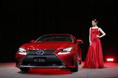 L'actrice Riyo Mori aux côtés du coupé hybride Lexus RC300h, lors du 43e salon automobile de Tokyo. La marque de luxe de Toyota anticipe dans les années à venir une hausse annuelle de ses ventes comprise entre 5% et 10%. /Photo prise le 20 novembre 2013/REUTERS/Toru Hanai