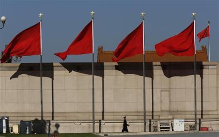 A Paramilitary soldier walks underneath red flags on the Tiananmen square next to the Great Hall of the People where the Chinese Communist Party plenum is being held in Beijing, November 12, 2013. REUTERS/Kim Kyung-Hoon