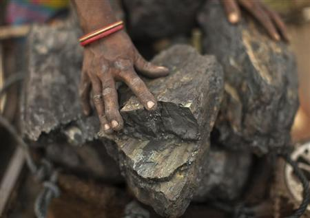 A local woman prepares to carry coal at an open coal field at Dhanbad district in Jharkhand September 19, 2012. REUTERS/Ahmad Masood/Files