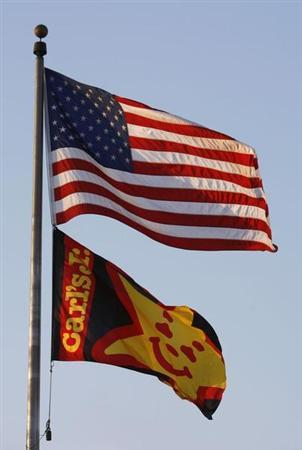 A Carl's Jr. fast food restaurant flag flies with a U.S. flag in Los Angeles, California May 11, 2012. REUTERS/David McNew