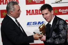 Barcelona's soccer player Lionel Messi (R) receives the Golden Boot trophy from former player Hristo Stoichkov during an award ceremony in Barcelona November 20, 2013. REUTERS/Albert Gea