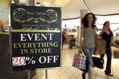 Pessoas carregam sacolas de compra e passam por uma placa que indica uma promoção no shopping Beverly Center em Los Angeles, Califórnia. Um indicador dos gastos dos consumidores dos Estados Unidos subiu mais que o esperado em outubro, sugerindo que a maior economia do mundo ganhou impulso no início do quarto trimestre. 8/11/2013 REUTERS/David McNew