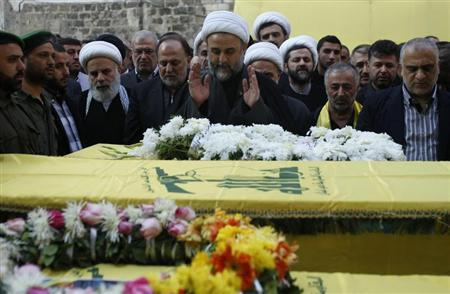 Lebanon's senior Hezbollah official Sheikh Nabil Qawouq (C) leads the prayer accompanied with Hezbollah parliament member Ali Ammar (centre L) around the coffins of four of the victims who were killed during two suicide bombings that occurred on Tuesday near Iran's embassy compound in Beirut, during their funeral November 20, 2013. REUTERS/ Sharif Karim