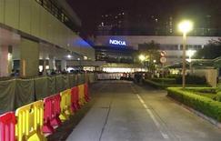 Cerca de cem trabalhadores em protesto são vistos do lado de fora da entrada principal de uma fábrica da Nokia em Dongguan, na província de Guangdong. Centenas de trabalhadores chineses protestavam nesta quarta-feira em frente a uma fábrica da Nokia, no sul da China, contra o que chamam de remuneração injusta, após a empresa vender seus negócios de telefonia móvel para a Microsoft. 20/11/2013 REUTERS/James Pomfret
