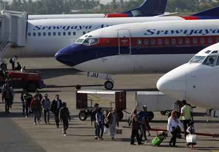 Passengers walk to their plane on the tarmac of Soekarno-Hatta airport in Jakarta, April 29, 2013. REUTERS/Beawiharta