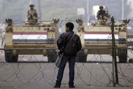 A man stands in front of a barbed wire fence set up by soldiers standing guard on armoured personnel carriers (APC) on Mohamed Mahmoud Street, near Tahrir Square in Cairo, November 20, 2013. REUTERS/Amr Abdallah Dalsh
