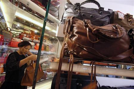 A customer checks a luxury handbag at a Milan Station outlet in Hong Kong September 2, 2013. REUTERS/Bobby Yip