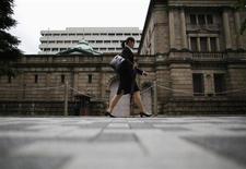 Женщина проходит мимо здания Банка Японии в Токио 2 июля 2012 года. Банк Японии сохранил ультрамягкую денежно-кредитную политику и вновь заявил об умеренном восстановлении экономики, подтвердив признаки восстановления экспорта, который является жизненно важным фактором для поддержания полученного благодаря мерам премьер-министра Синдзо Абэ импульса. REUTERS/Toru Hanai