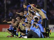 Игроки сборной Уругвая празднуют выход в финальную часть чемпионата мира в Монтевидео 20 ноября 2013 года. Уругвай получил право участвовать в финальной части чемпионата мира 2014 года, по сумме двух игр обойдя Иорданию. REUTERS/Andres Stapff