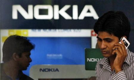 A customer speaks on his mobile phone as he comes out of a Nokia showroom in New Delhi March 28, 2013. REUTERS/Mansi Thapliyal