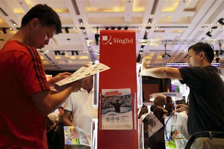 People look at brochures for deals on offer at the SingTel roadshow during the annual IT Show technology fair in Singapore March 10, 2012. REUTERS/Tim Chong