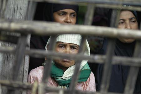 Rohingya Muslim women look out from their home at Aung Mingalar quarter in Sittwe August 13, 2013. REUTERS/Soe Zeya Tun