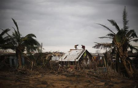 Fishermen and their family members repair the roof of their houses at the cyclone-hit Nalianuagaon village in Ganjam district in the eastern Indian state of Odisha October 15, 2013. REUTERS/Adnan Abidi