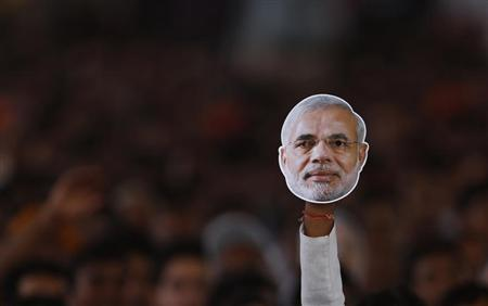 A supporter of India's main opposition Bharatiya Janata Party (BJP) holds a mask of Hindu nationalist Narendra Modi, prime ministerial candidate for BJP and Gujarat's chief minister during a rally being addressed by Modi in New Delhi September 29, 2013. REUTERS/Adnan Abidi