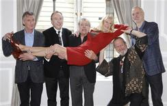 The surviving members of the original cast of the Monty Python comedy team (L-R) Michael Palin, Eric Idle, Terry Jones,Terry Gilliam and John Cleese, hold Carol Cleveland as they pose for photographers at a photocall in central London November 21, 2013. REUTERS/Luke MacGregor