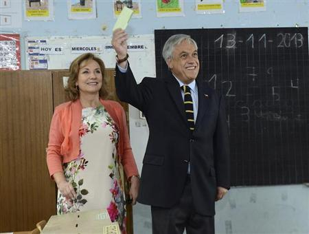 Chile's President Sebastian Pinera (R) accompanied by first lady Cecilia Morel shows his vote during the presidential election at a school in Santiago, November 17, 2013. REUTERS/Presidencia/Handout